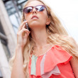 Attractive young blonde woman talking on the phone outdoor — Stock Photo