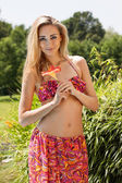 Attractive young blond woman summer outdoor with flower — Stock Photo