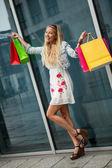 Glimlachend blonde vrouw met kleurrijke tassen over shopping tour — Stockfoto