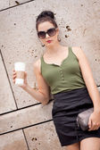 Attractive young woman with smartphone and sunglasses outdoor — Stock Photo