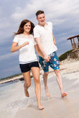 Happy young couple on the beach in summer holiday love — Stock Photo