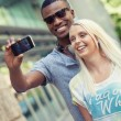 Young smiling multiracial couple taking foto by smartphone  — Foto Stock