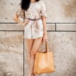 Attractive young brunette woman in sexy dress and handbag  — Стоковая фотография