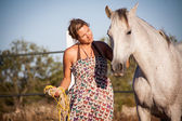 Young woman walking a road with horse — Stock Photo