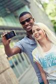 Jung lächelnd vielpunkt paar Foto, indem wir smartphone — Stockfoto