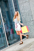 Smiling blonde woman with colorful bags on shopping tour — Стоковое фото