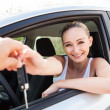 Young smiling womsitting in car taking key — Stock Photo #34764265