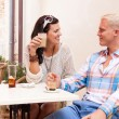 Happy young couple sitting outside cafe restaurant drinking coffee — Stock Photo