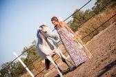 Joven mujer caminando un camino con caballo — Foto de Stock