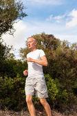 Athletic man runner jogging in nature outdoor — ストック写真