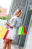 Smiling blonde woman with colorful bags on shopping tour — Stock Photo