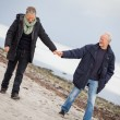 Mature happy couple walking on beach in autumn — Stock Photo