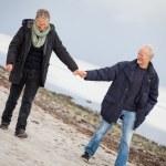 Mature happy couple walking on beach in autumn — Stock Photo #34771369