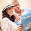 Young attractive tourist couple with city map in summer — Stock Photo