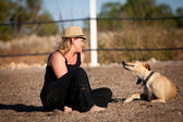 Smiling blonde woman sitting outdoor with her dog — Stock Photo