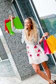 Usmíval se blonďatá žena s barevné tašky na nákupy turné — Stock fotografie