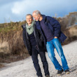 Mature senior couple walking on the beach autumn winter — Stock Photo