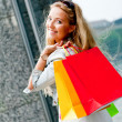 Smiling blonde woman with colorful bags on shopping tour — Stockfoto