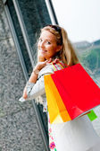 Mulher loira com sacos coloridos na tour de compras a sorrir — Fotografia Stock