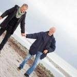 Mature happy couple walking on beach in autumn — Stock Photo #36606927