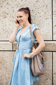 Young smiling woman talking on mobile phone smartphone — Stock Photo