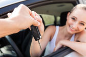 Young smiling woman sitting in car taking key — Stock Photo