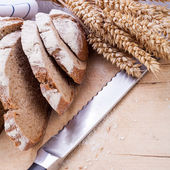 Homemade fresh baked bread and knife — Stock Photo