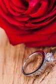 Schöne Ring auf hölzernen Hintergrund und rote rose — Stockfoto