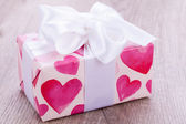 Pretty Valentines gift with hearts on the giftwrap — Stock Photo