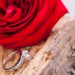 Beautiful ring on wooden background and red rose — Stock Photo #37936193