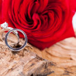 Beautiful ring on wooden background and red rose — Stock Photo #37985209