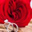 Beautiful ring on wooden background and red rose — Stock Photo #37985261