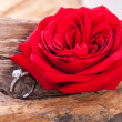 Beautiful ring on wooden background and red rose — Stock Photo