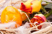 Vivid orange Easter egg with a gerbera and rose — Stock Photo