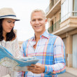 Young couple of tourists consulting a map — Stock Photo #37990077