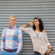 Stock Photo: Fashionable couple posing in front of metal door