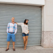 Fashionable couple posing in front of a metal door — Stock Photo #37990235