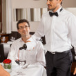 Постер, плакат: Waiter serving a couple in a restaurant