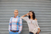 Fashionable couple posing in front of a metal door — Stock Photo