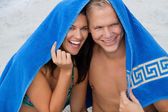 Cheerful couple with a towel covering their heads — Stock Photo