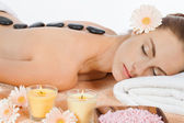 Attractive healthy caucasian woman hot stone massage wellness — Stock Photo