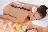 Young attractive woman get hot stone massage — Stock Photo