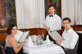 Young smiling couple at the restaurant — Stock Photo