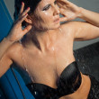 Stock Photo: Womin black lingerie dripping water