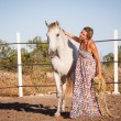 Stock Photo: Young womtraining horse outside in summer