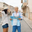 Young couple of tourists consulting a map — Stock Photo