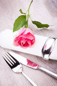 Table setting with a single pink rose — Stock Photo