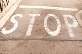 Stop painted on asphalt outdoor — Stock Photo