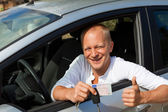 Excited driver holding the keys of his new car — Stock Photo