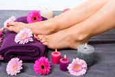 Bare feet of a woman surrounded by flowers — Stock Photo